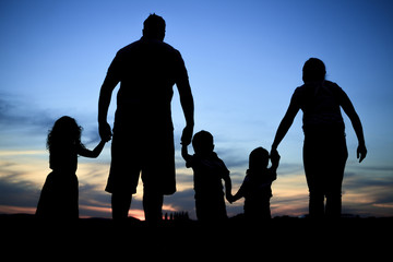 Silhouette of a young family with some childs standing