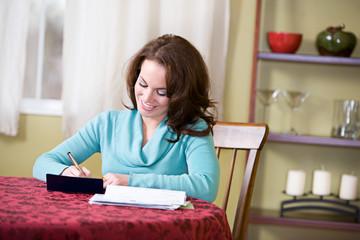 Finances: Woman Writing Checks To Pay Bills