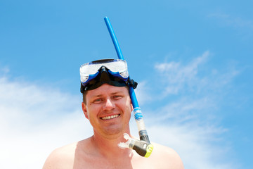 Young man smiling while standing on the beach in equipment for s