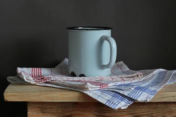 кружка и полотенце на деревянном столе
