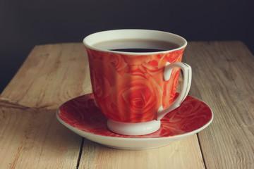 красная чашка с чаем на деревянном столе