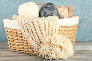 Knitting scarf and yarn in basket, on wooden background