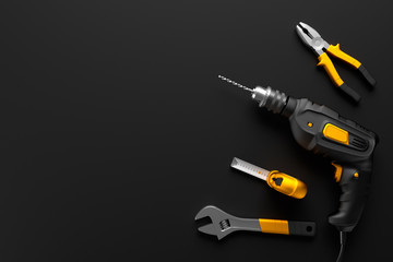 drill, wrench and construction tools on the black background tex
