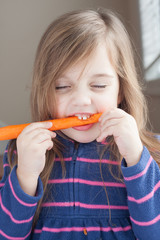 little girl eating a long carrot