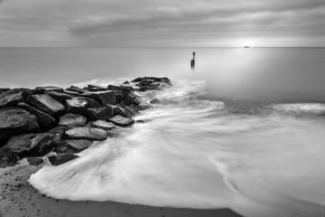 Milky waves splashing over rocks in black and white