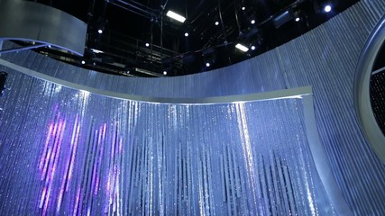 Tilt up from shiny beaded curtain to lights on stage