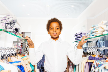 African boy in white shirt stand between hangers
