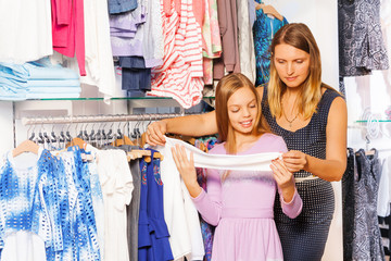 Smiling girl with her mother shopping together