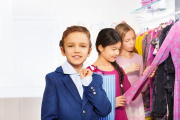 Two girls and one boy with shopping bag in store
