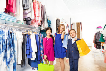 Two smiling girls and boy with shopping bags