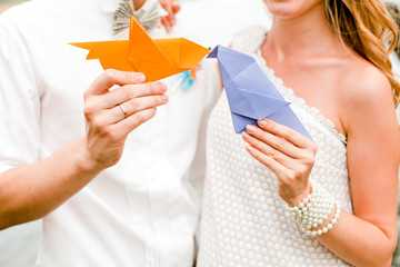 Couple holding paper origami birds