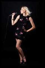 Beautiful young woman  with microphone singing in karaoke