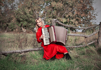 Retro woman in traditional costume with an accordion, in a field