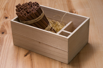 A bunch of cinnamon sticks in a wooden box