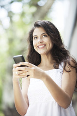 Beautiful Latin Woman Smiling with Cel Phone