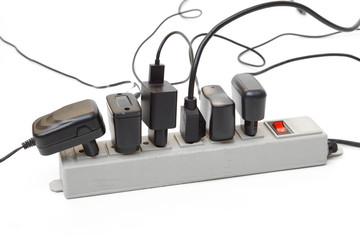 Many plugs and adapters plugged into electric power bar