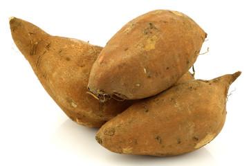 three sweet potatoes on a white background