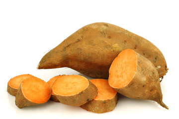 whole sweet potato and a cut one on a white background