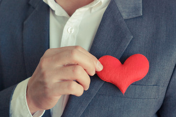 Businessman pulling out a red heart from the pocket of his suit