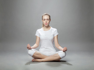 meditating blonde woman on gray background