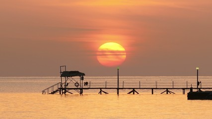 beautiful sunrise over pier in sea - filmed at telephoto lens 4k