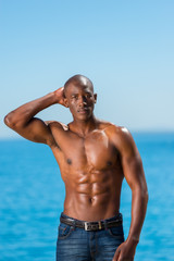 Topless African black man standing on rock