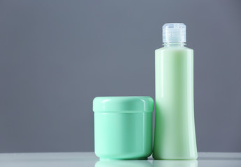 Cosmetic bottles on grey background