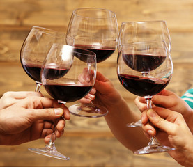 Clinking glasses of red wine in hands