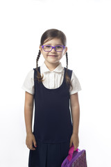 A young girl in uniform is ready for her first day of school.