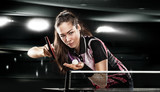 Fototapety Young pretty sporty girl playing table tennis on black