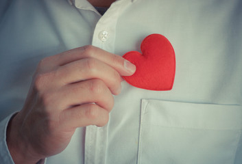 Businessman pulling out red heart from the pocket of his shirt