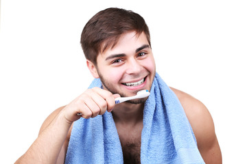Portrait of young man with toothbrush in hand isolated on white