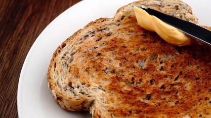 Spreading creamy cheese spread on healthy whole grain toast