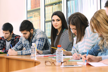 Group of students sitting at table in library