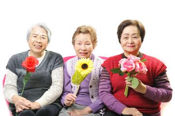 綺麗なお花を持って座っている高齢者の女性三人組