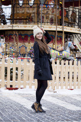 Happy young brown haired woman on the background of a winter amu