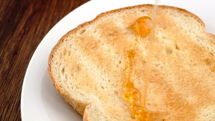 Delicious honey drizzling on freshly toasted bread