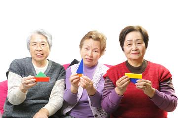 積み木を持って遊んでいる3人の高齢者の女性