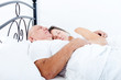 elderly couple sleeping in bed.