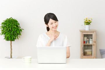 パソコンの前で想像する女性