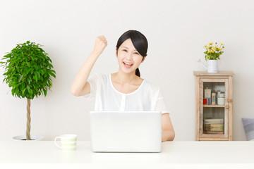 パソコンの前でガッツポーズする女性