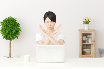 パソコンの前でバツ印する女性