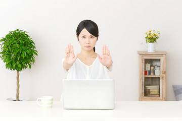 パソコンの前で制止する女性