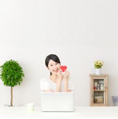 パソコンの前でハートを持つ女性