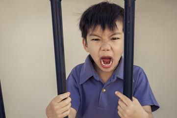 Angry boy behind a iron bar