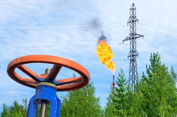 Oil field. The valve with a gas torch on a background.