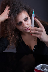 Young woman with drug addiction on dark background
