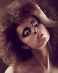 Dreamy Woman with Frizzy Hairstyle and Golden Eyeshadow