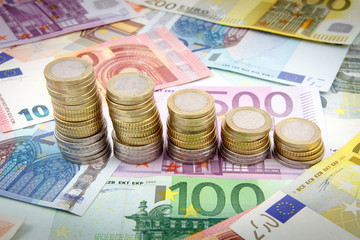 Decreasing stacks of euro coins on euro banknotes