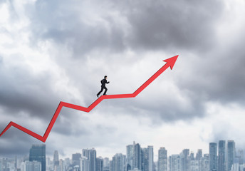 Young businessman running on chart arrow going up